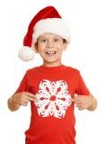 El muchacho en retrato del sombrero de santa con el copo de nieve grande en blanco aisló - concepto de la Navidad de las vacacion Fotos de archivo