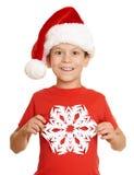 El muchacho en retrato del sombrero de santa con el copo de nieve grande en blanco aisló - concepto de la Navidad de las vacacion Imagen de archivo
