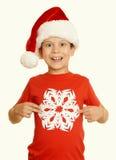 El muchacho en retrato del sombrero de santa con el copo de nieve grande en blanco aisló - el concepto de la Navidad de las vacac Foto de archivo