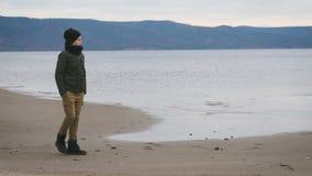 El muchacho en ropa caliente está caminando a lo largo de la costa de la costa que mira soñador el agua con las montañas en almacen de metraje de vídeo