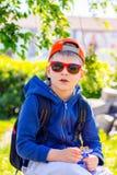 El muchacho en ropa elegante con las gafas de sol y la mochila descansará d Imágenes de archivo libres de regalías