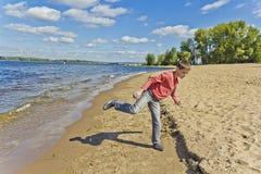 El muchacho en rosa está lanzando la arena en una playa Fotos de archivo libres de regalías