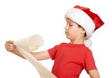 El muchacho en sombrero rojo con la voluta larga desea a santa - concepto de la Navidad de las vacaciones de invierno Foto de archivo