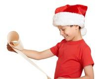 El muchacho en sombrero rojo con la voluta larga desea a santa - concepto de la Navidad de las vacaciones de invierno Imagen de archivo