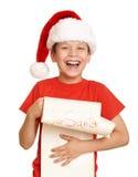 El muchacho en sombrero rojo con la voluta larga desea a santa - concepto de la Navidad de las vacaciones de invierno Imágenes de archivo libres de regalías