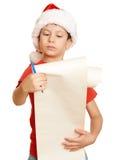 El muchacho en sombrero rojo con la voluta larga desea a santa - concepto de la Navidad de las vacaciones de invierno Fotos de archivo