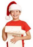 El muchacho en sombrero rojo con la voluta larga desea a santa - concepto de la Navidad de las vacaciones de invierno Imagenes de archivo