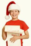 El muchacho en sombrero rojo con la voluta larga desea a santa - el concepto de la Navidad de las vacaciones de invierno, amarill Imágenes de archivo libres de regalías