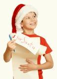 El muchacho en sombrero rojo con la voluta larga desea a santa - el concepto de la Navidad de las vacaciones de invierno, amarill Fotos de archivo libres de regalías