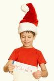 El muchacho en sombrero rojo con la voluta larga desea a santa - el concepto de la Navidad de las vacaciones de invierno, amarill Foto de archivo libre de regalías