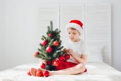 El muchacho en el sombrero rojo de Papá Noel adorna bolas pequeñas de un árbol de navidad Fotografía de archivo libre de regalías