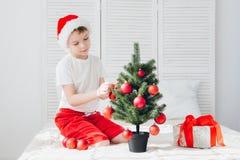 El muchacho en el sombrero rojo de Papá Noel adorna bolas pequeñas de un árbol de navidad Fotografía de archivo