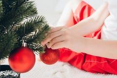 El muchacho en el sombrero rojo de Papá Noel adorna bolas pequeñas de un árbol de navidad Imagen de archivo libre de regalías