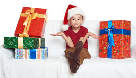 El muchacho en sombrero rojo del ayudante de santa con las cajas de regalo hace un deseo - concepto del día de fiesta de la Navid Foto de archivo