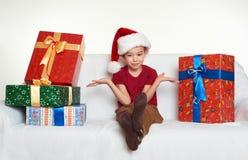 El muchacho en sombrero rojo del ayudante de santa con las cajas de regalo se sienta en el sofá Fondo blanco Concepto del día de  Fotos de archivo