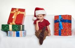El muchacho en sombrero rojo del ayudante de santa con las cajas de regalo se sienta en el sofá Fondo blanco Concepto del día de  Fotografía de archivo
