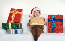 El muchacho en sombrero rojo del ayudante de santa con las cajas de regalo se sienta en el sofá Fondo blanco Concepto del día de  Imágenes de archivo libres de regalías