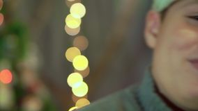 El muchacho en el suéter y el sombrero de las risas de Santa Claus Primer, contra la perspectiva de luces de la Navidad almacen de video