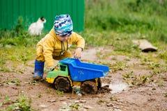 El muchacho en el traje amarillo que juega con un coche del juguete en la suciedad imagen de archivo