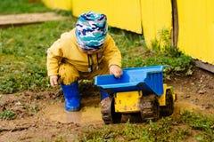El muchacho en el traje amarillo que juega con un coche del juguete en la suciedad imágenes de archivo libres de regalías