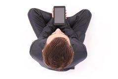 El muchacho en traje negro sienta y sostiene la tableta Imágenes de archivo libres de regalías