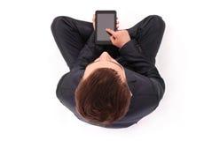 El muchacho en traje negro sienta y sostiene la tableta Foto de archivo libre de regalías