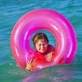 El muchacho en un anillo de la nadada se divierte Imagen de archivo libre de regalías