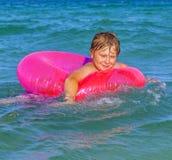 El muchacho en un anillo de la nadada se divierte Fotografía de archivo