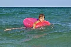 El muchacho en un anillo de la nadada se divierte Imagenes de archivo