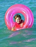 El muchacho en un anillo de la nadada se divierte en el ocea Foto de archivo