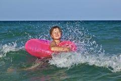 El muchacho en un anillo de la nadada se divierte en el ocea Imágenes de archivo libres de regalías