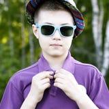 El muchacho en un casquillo y vidrios Foto de archivo