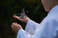 El muchacho en un kimono lleva a cabo un incienso ardiente, palillo y un budista sea Fotos de archivo