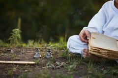 El muchacho en un kimono se sienta en una posición de loto que medita en el otoño, r Fotos de archivo