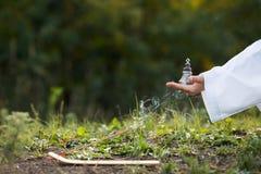 El muchacho en un kimono sostiene un palillo ardiente del incienso, realizando un myst Foto de archivo libre de regalías