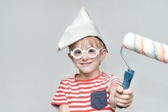 El muchacho en un sombrero de papel está jugando en un pintor Retrato Rodillo para pintar Fotografía de archivo libre de regalías