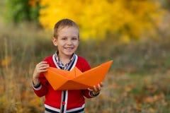 El muchacho en un suéter rojo está sosteniendo un barco del papel grande y sonríe Fotografía de archivo libre de regalías