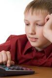 El muchacho en una camisa roja piensa en la calculadora Imagenes de archivo