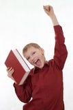El muchacho en una camisa roja salta de un libro Fotografía de archivo libre de regalías