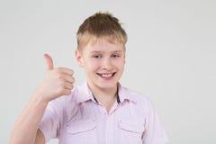El muchacho en una camisa rosada haciendo los pulgares para arriba Foto de archivo libre de regalías