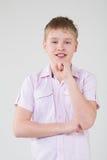 El muchacho en una camisa rosada que apoya para arriba la mano a la cabeza Fotos de archivo
