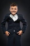 El muchacho en una chaqueta negra del traje corrige Imagenes de archivo