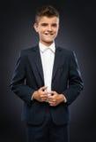 El muchacho en una chaqueta negra del traje corrige Fotografía de archivo libre de regalías