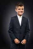 El muchacho en una chaqueta negra del traje corrige Foto de archivo