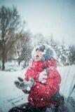 El muchacho en una nieve acumulada por la ventisca sienta y coge una boca del copo de nieve Foto de archivo