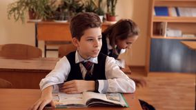 El muchacho en uniforme en la sala de clase aumenta su mano incierto que contestaría al profesor metrajes