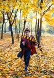 El muchacho en vidrios corre en parque del otoño con las hojas del oro, sostiene el libro en sus manos, lleva en traje negro imagenes de archivo