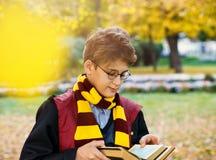 El muchacho en vidrios se coloca en parque del otoño con las hojas del oro, sostiene el libro en sus manos fotos de archivo libres de regalías