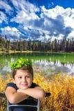 El muchacho encantador se sienta en la orilla del pequeño lago Fotos de archivo