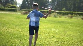El muchacho enciende un avión del juguete en el parque Cámara lenta almacen de metraje de vídeo